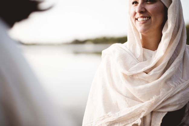 예수 그리스도와 이야기하는 동안 성경 가운을 입고 여성의 얕은 초점 샷