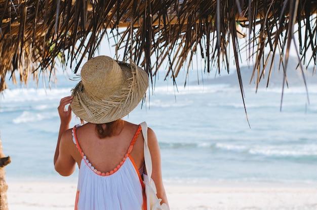 Неглубокий снимок женщины в сарафане, стоящей под навесом на пляже