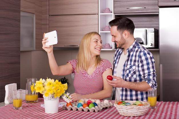 喜びでイースターエッグを描いている間自分撮りをしている幸せなカップルの浅いフォーカスショット