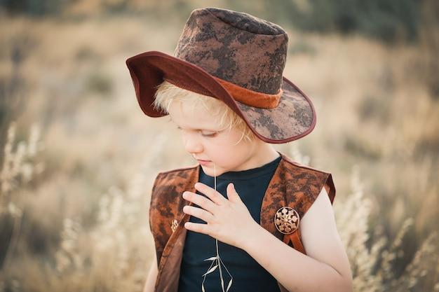 茶色の帽子をかぶった小さなブロンドの髪の少年の浅いフォーカスショット