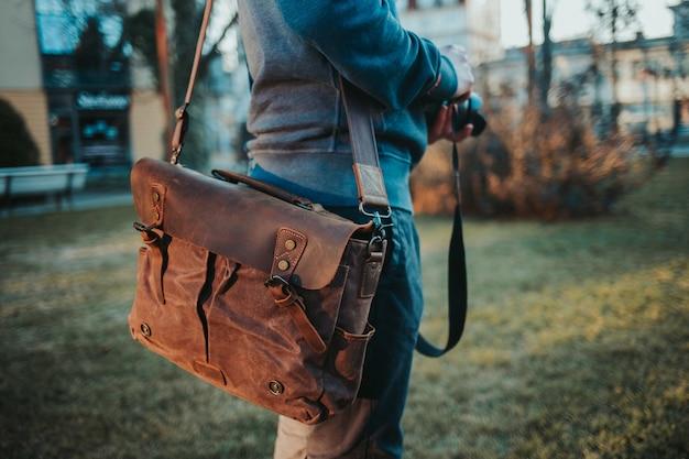 Неглубокий снимок мужчины в коричневой кожаной сумке с фотоаппаратом в руках