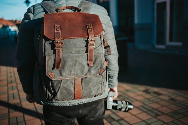 Неглубокий снимок мужчины в серо-коричневом рюкзаке