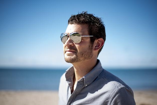 晴れた日にビーチでサングラスをかけている男性の浅いフォーカスショット