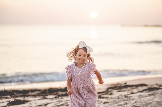 해변에 작은 금발 소녀의 얕은 초점 샷