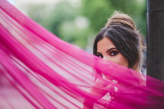 카메라에 포즈를 취하는 분홍색 드레스를 입은 젊은 백인 여성의 얕은 초점