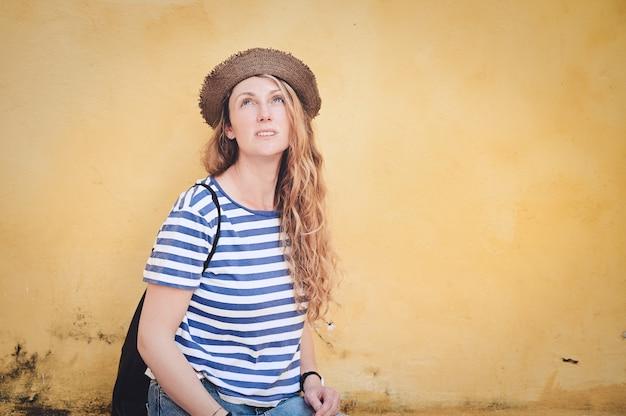 노란색 벽에 젊은 금발 여성의 얕은 초점 샷