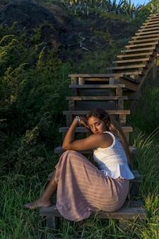 カメラでポーズをとる若い白人女性の浅いフォーカスショット