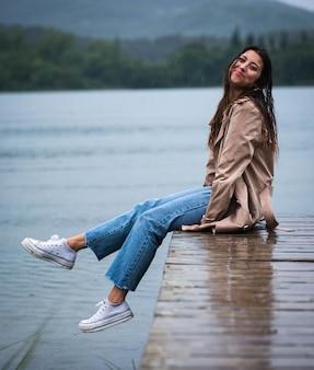 빗속의 나무 부두에 앉아 있는 젊은 여성의 얕은 초점