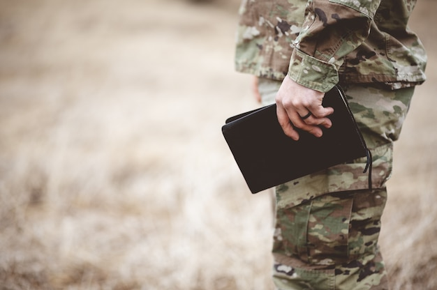 フィールドで聖書を持っている若い兵士の浅いフォーカスショット