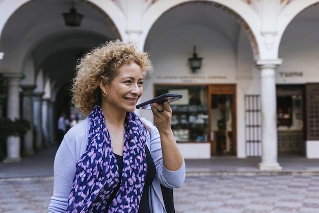 通りを歩きながら電話で話している大人のヒスパニック系女性の浅いフォーカスショット