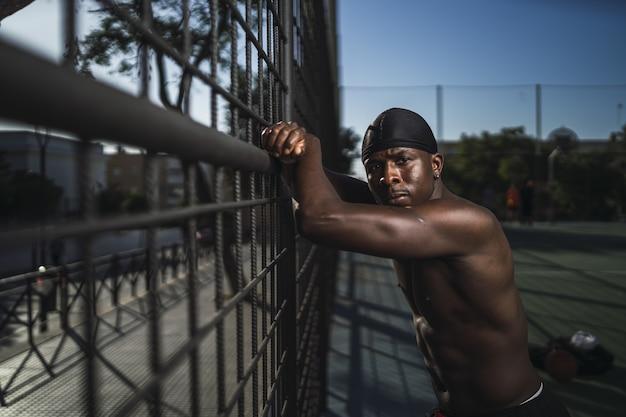 フェンスに寄りかかって半裸のアフリカ系アメリカ人男性の浅いフォーカスショット