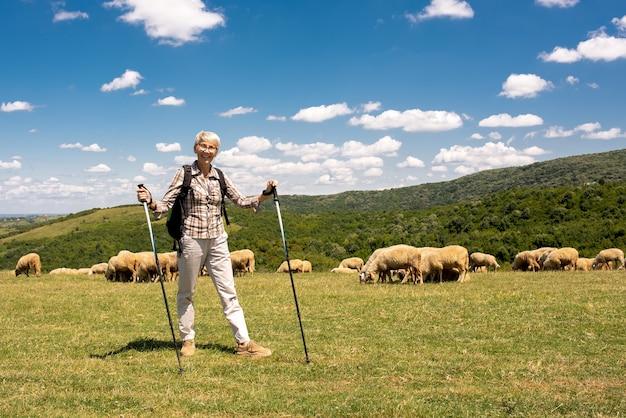 大きな野原で年配の女性旅行者の浅いフォーカス ショット