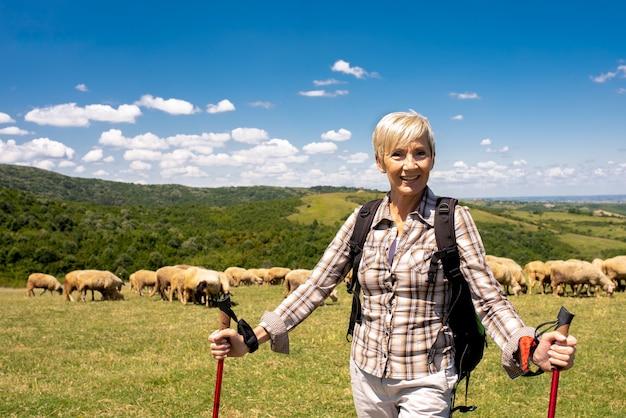 Неглубокий снимок пожилой путешественницы в большом поле