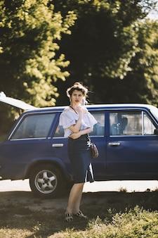 Неглубокий фокус выстрел привлекательной женской модели в платье с открытыми плечами, позирует возле транспортного средства