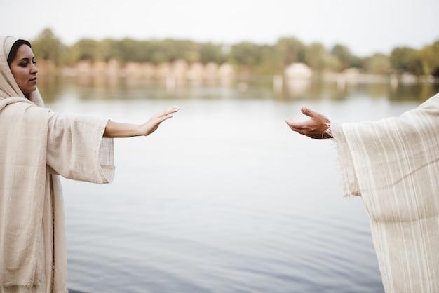 聖書のガウンを着て、イエス・キリストの手に手を伸ばす女性の浅いフォーカスショット
