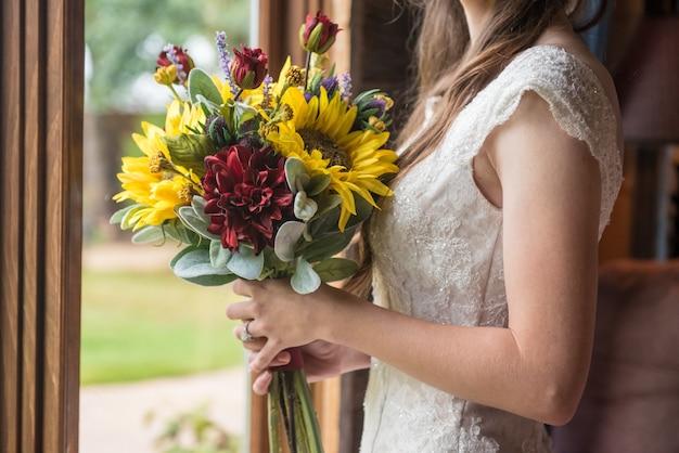 Неглубокий снимок невесты, держащей красивый букет с подсолнухами