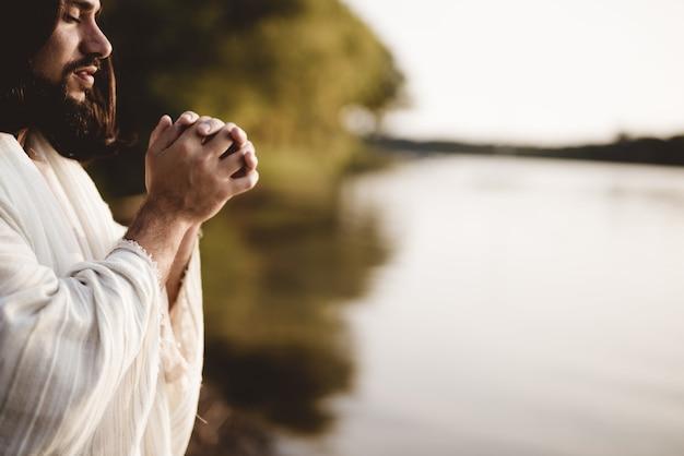 그의 눈을 감고있는 동안기도하는 예수 그리스도의 얕은 초점 샷