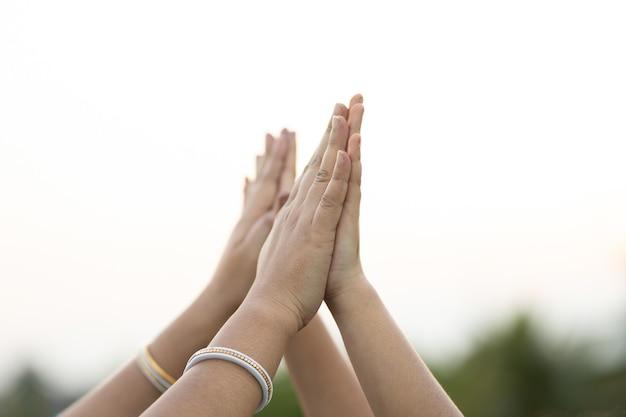 Inquadratura poco profonda di persone che si uniscono ai palmi su uno sfondo sfocato