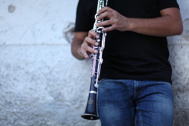 Colpo poco profondo del fuoco di una persona che gioca il clarinetto davanti a un muro bianco