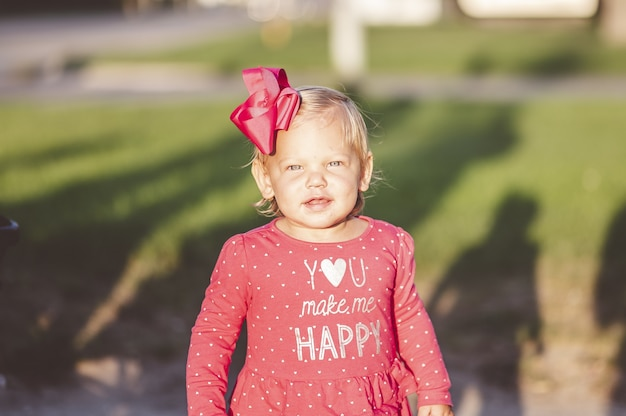 Shallow focus shot of a smiling young girl wearing a cute bow