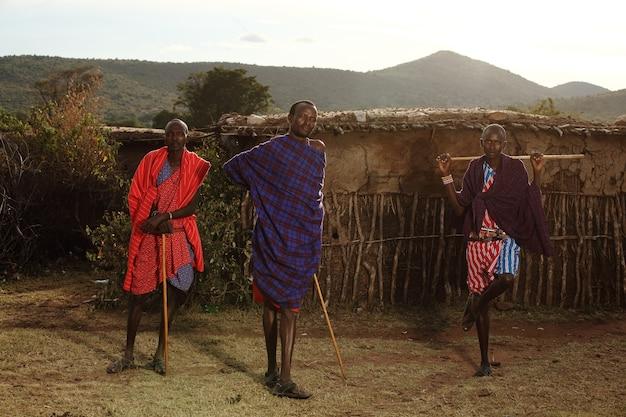 Messa a fuoco poco profonda di tre maschi africani che tengono dei bastoni