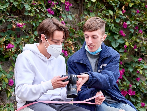 A shallow focus shot of two young caucasian males watching photos on camera in the park