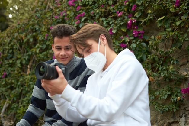 A shallow focus shot of two young males watching photos on camera in the park