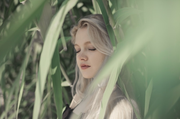 Shallow focus shot of a young blonde female with closed eyes behind the green leaves