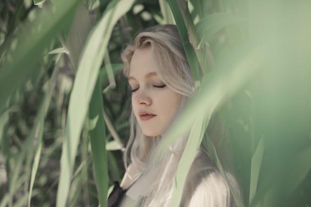 Colpo poco profondo del fuoco di una giovane femmina bionda con gli occhi chiusi dietro le foglie verdi