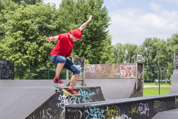 Inquadratura poco profonda di un giovane ragazzo che fa skateboard in città
