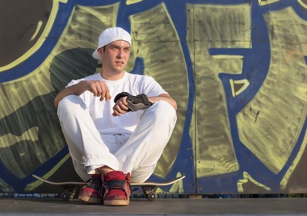 Colpo poco profondo del fuoco di un giovane ragazzo che pattina nella zona dello skateboard