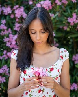 Inquadratura poco profonda di una giovane donna bruna con fiori rosa in mano