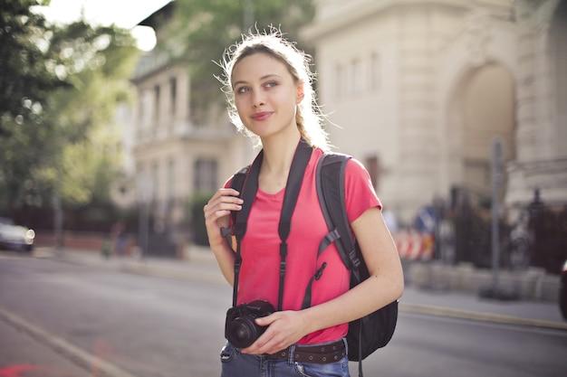Colpo poco profondo del fuoco di una giovane donna che fa un giro della città e che tiene in mano una macchina fotografica