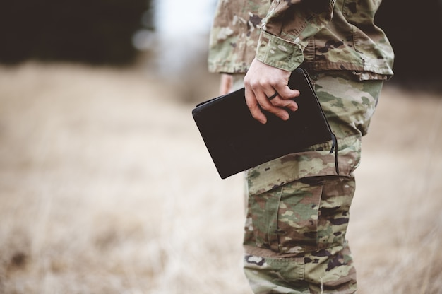 Shallow focus shot of a young soldier holding a bible in a field