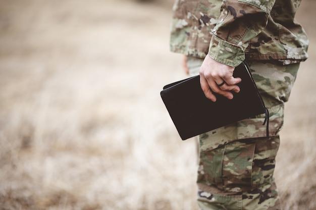 Colpo poco profondo del fuoco di un giovane soldato che tiene una bibbia in un campo