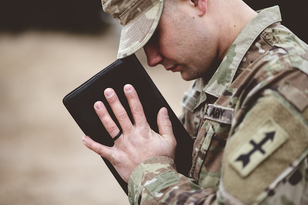 Colpo poco profondo del fuoco di un giovane soldato che prega mentre tiene la bibbia