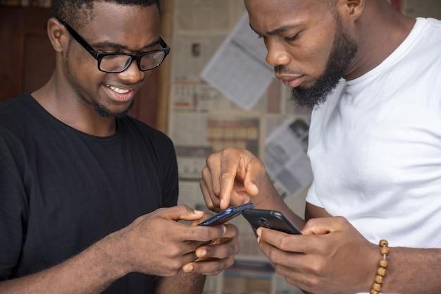 Messa a fuoco superficiale di due giovani maschi africani che condividono contenuti attraverso i loro telefoni