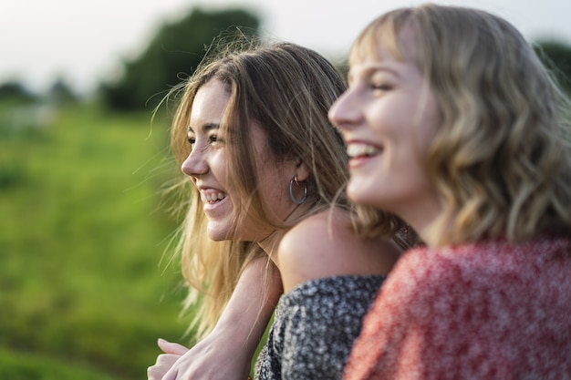 Fuoco poco profondo di due giovani donne allegre che si abbracciano in un parco in spagna