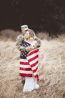 Colpo verticale del fuoco poco profondo di un soldato americano che abbraccia la sua moglie