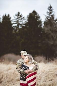 妻を抱き締めるアメリカ兵の浅い焦点の垂直ショット