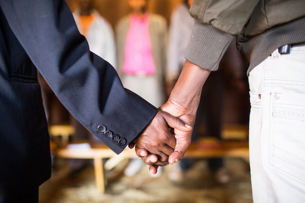 Shallow focus view of two people holding hands with each other