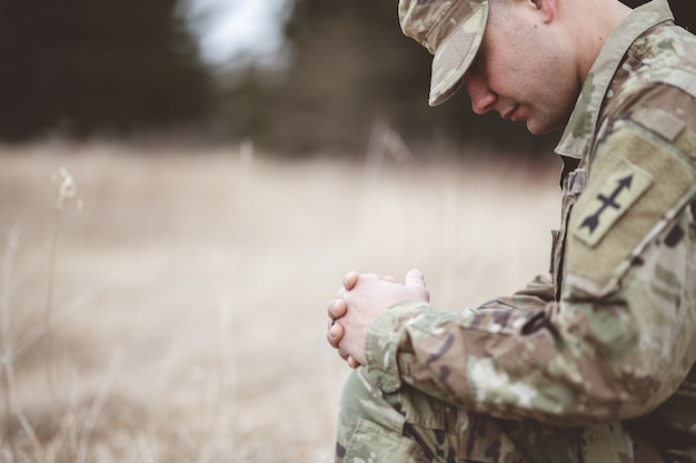 Shallow focus of a young soldier praying while kneeling on a dry grass
