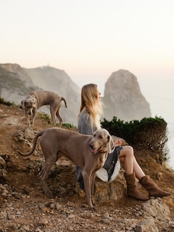 Shallow focus of a young woman with weimaraners sitting on the shore surrounded by the sea