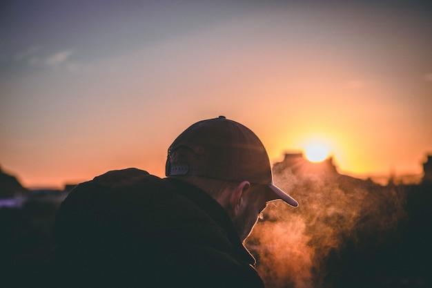 日没の黄金の時間の間に帽子をかぶった男の背中の浅い焦点を合わせたショット。