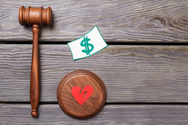 Поддельная концепция фальшивого брака. молоток со знаком доллара и разбитым сердцем.