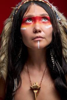 Shaman looking up having colourful paintings on face, wearing ethnic traditional indian costume,isolated
