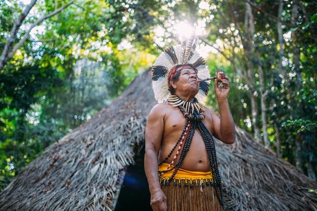 パタクセ族のシャーマン、羽飾りを身に着け、パイプを吸う