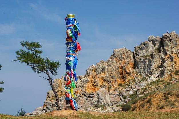 Olkhon 섬 케이프 burkhan의 배경에 여러 가지 빛깔의 리본이 달린 주술사 기둥. olkhon 섬의 케이프 burkhan에 13 개의 기둥.
