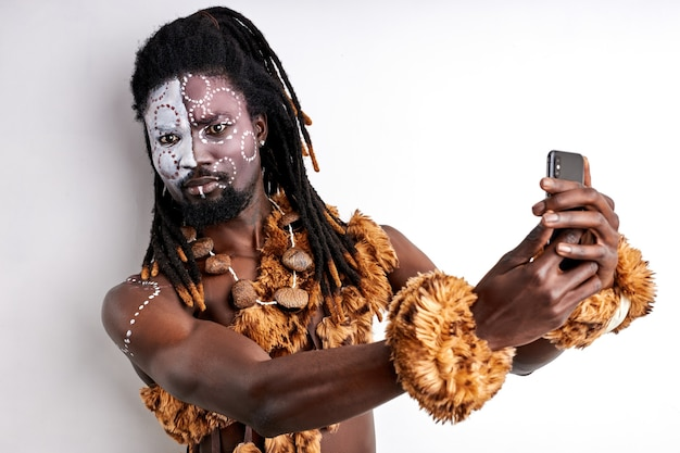 Shaman uses mobile phone, try to study its front, having ethnic paintings on face