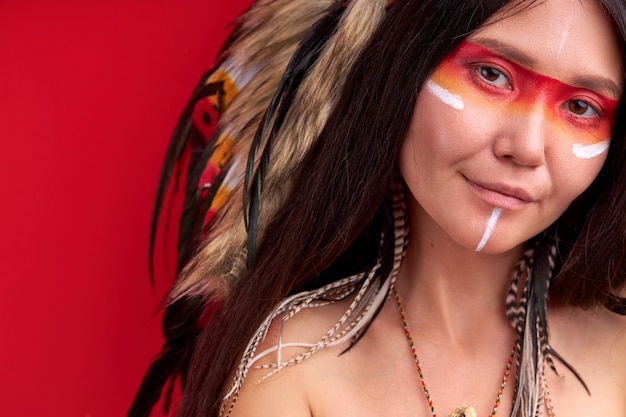 Shaman woman with feathers on head looks at front smiling, having ethnic indian paintings on face. isolated red wall